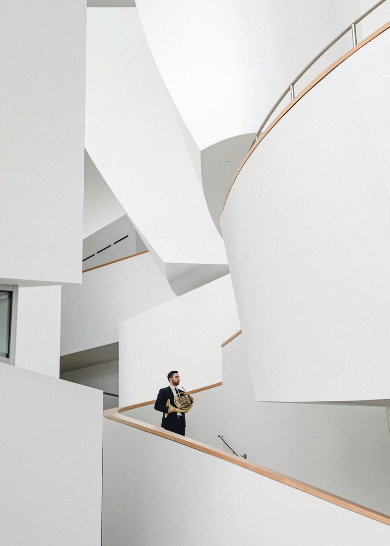 Horn player Corbin Castro on the stairwell of the New World Center. NEW WORLD SYMPHONY PHOTO BY BEN DIAZ